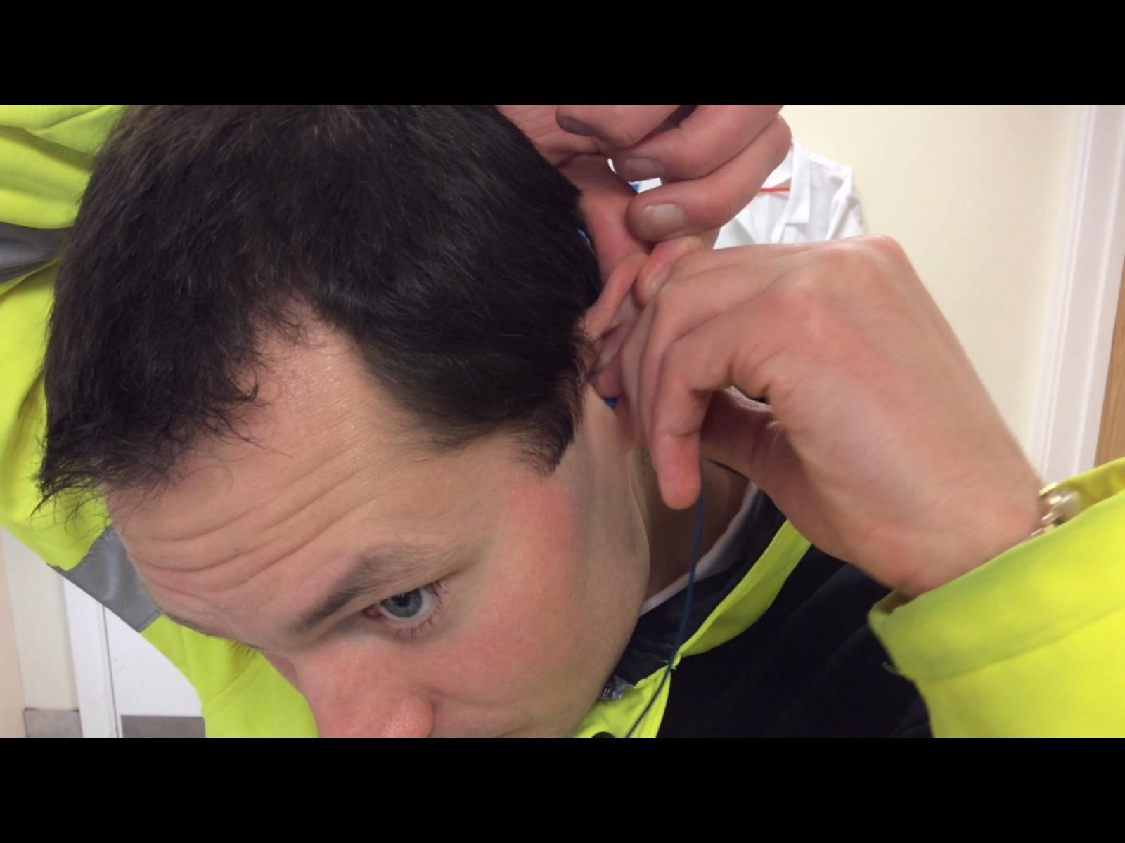 Man inserting earplug into ear canal